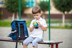 Piccolo scolaro sveglio che studia all'aperto il giorno soleggiato Immagini Stock Libere da Diritti