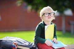 Piccolo scolaro sveglio che studia all'aperto il giorno soleggiato Di nuovo al concetto del banco Fotografie Stock