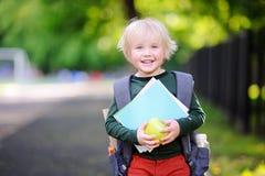 Piccolo scolaro sveglio con il suoi zaino e mela Di nuovo al concetto del banco Fotografia Stock