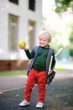 Piccolo scolaro sveglio con il suoi zaino e mela Di nuovo al concetto del banco Immagine Stock Libera da Diritti