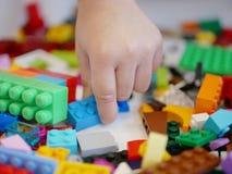 Piccolo selezionamento/che sceglie della mano del ` s del bambino un pezzo di mattoni di plastica di collegamento variopinti fotografia stock