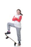 Piccolo skateboarder allegro che posa con i pollici su immagine stock