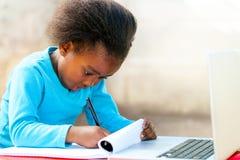 Piccolo studente africano che fa compito Fotografia Stock