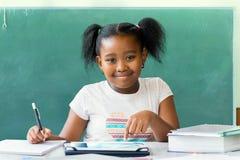 Piccolo studente africano che si siede allo scrittorio con il bordo nero in bianco dentro Immagini Stock