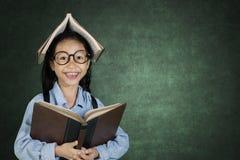 Piccolo studente che sorride alla macchina fotografica in aula Fotografia Stock Libera da Diritti