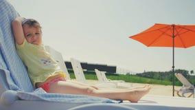 Piccolo sunbath felice della presa della neonata in sedia alla spiaggia stock footage