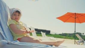 Piccolo sunbath felice della presa della neonata in sedia alla spiaggia archivi video