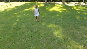 Piccolo una ragazza felice di quattro anni sta correndo sull'erba verde nel parco archivi video