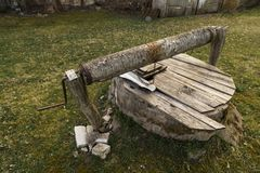 Piccolo vecchio pozzo di legno su erba vicino ad un werehouse di legno immagine stock