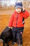 Piccolo viaggiatore divertente con un sacchetto e un cell-phone fotografia stock