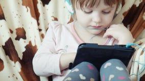 Piccolo video sveglio dell'orologio della ragazza sulla compressa digitale stock footage