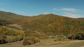Piccolo villaggio nelle montagne Belle colline e foresta di conifere arancio stock footage