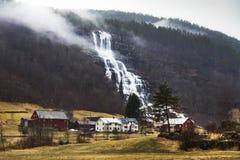 Piccolo villaggio norvegese e una cascata potente Fotografia Stock