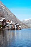Piccolo villaggio su una costa del lago vicino alle montagne Immagini Stock