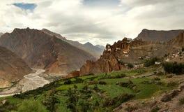 Piccolo villaggio sul pendio della valle della montagna con il fiume e l'azienda agricola dentro dentro Fotografia Stock