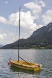 Piccolo yacht giallo di navigazione sul lago alpino Mondsee in Austria Fotografia Stock