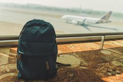 Piccolo zaino blu che sta sul pavimento all'aeroporto immagini stock