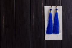 Piccolo zaino del ` s della donna del cuoio bianco ed orecchini blu del filo Fotografie Stock