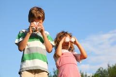 Pièce de fille et de garçon avec de petites bouteilles Photographie stock libre de droits