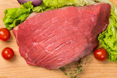 Pice of fresh raw meat with vegetables. Pice of fresh raw meat with lettuce, cherry, onion on wooden board Stock Photography