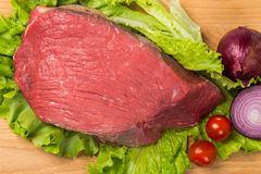 Pice of fresh raw meat with vegetables. Pice of fresh raw meat with lettuce, cherry, onion on wooden board Royalty Free Stock Images