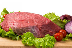 Pice of fresh raw meat with vegetables. Pice of fresh raw meat with lettuce, cherry, onion on wooden board Royalty Free Stock Photo
