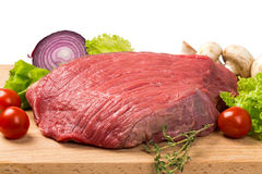 Pice of fresh raw meat with vegetables. Pice of fresh raw meat with lettuce, cherry, onion on wooden board Stock Image