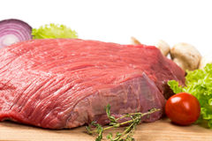 Pice of fresh raw meat with vegetables. Pice of fresh raw meat with lettuce, cherry, onion on wooden board Royalty Free Stock Photography