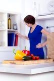 Épiceries déballées et une femme aux livres de cuisine Photo stock