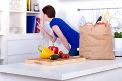 Épiceries déballées et une femme aux livres de cuisine Image stock
