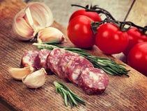 Épices et ail coupés en tranches de saucisse sur un conseil Photos libres de droits