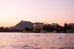 Pichola lake udaipur at dusk with aravali hills in background. Dusk shot of the hotel at the banks of lake pichola with aravali hills in the background. This is Stock Photography