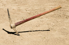 Pick Ax plunged into dirt ground Stock Photography