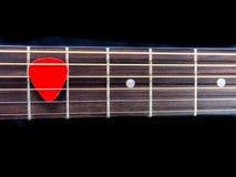 Pick guitar on finger board background. Pick guitar on finger board on black background Stock Photography