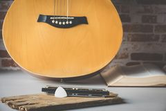 A pick of guitar on mouth organ with acoustic guitar background. Royalty Free Stock Images