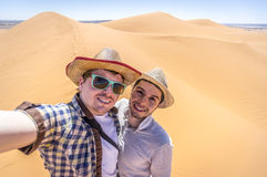 On the pick of the sand dune. Western tourists making selfie on the dune of Sahara desert Royalty Free Stock Images