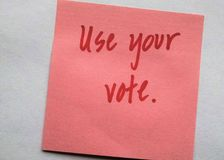 Handwritten red letters on plain background `Use your vote`. Pick sticky paper background with ruby red lettering is the message `Use your vote.` Off centered royalty free stock images
