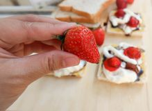 Pick strawberry or bread and canape with strawberry. Topping Royalty Free Stock Images