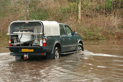 Pick up in a flood. 4x4 pick up driving to the dump in a flood - could possibly saving domestic posession from flooding Stock Photo
