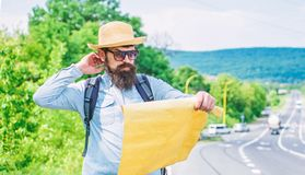 Pick up local map. Tourist backpacker looks at map choosing travel destination at road. Around the world. Find map large. Sheet of paper. Allow recognize enough royalty free stock photography