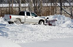 Moving lots of snow  on a cold winter day. A  pick up with a plow moves snow after a storm in Michigan USA Royalty Free Stock Photography