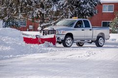 Plowing snow after a big storm. A  pick up with a plow moves snow after a storm in Michigan USA Royalty Free Stock Image