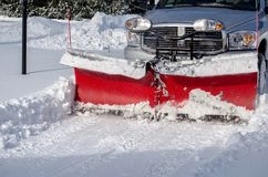 Snow blade closeup at work. A  pick up with a plow moves snow after a storm in Michigan USA Royalty Free Stock Photo