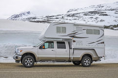 Truck camper. Pick-up truck camper on the road, snow covered mountains and snow and ice in background Royalty Free Stock Photography