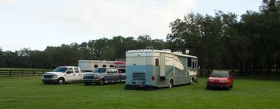 Pick-up trucks with horse trailers and a motor home parked inside a paddock in florida Royalty Free Stock Photos