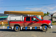A pick-up used for camping with a canoe tied to the top Stock Photography