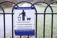 Pick Up Dog Mess Waste Sign in Public Countryside Park. Pick up after your dog sign in public park be responsible Royalty Free Stock Image