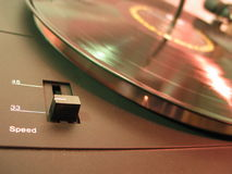 Pick your speed. Corner detail of a turntable with focus on the speed control - blurred record in the background with red and green highlights Royalty Free Stock Images