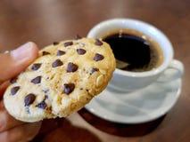 Pickd della mano del biscotto di pepita di cioccolato da dire con una tazza di caffè nero fotografia stock libera da diritti