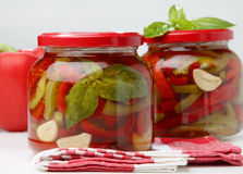 Pickeled green and red pepper in jar. On table Royalty Free Stock Photos